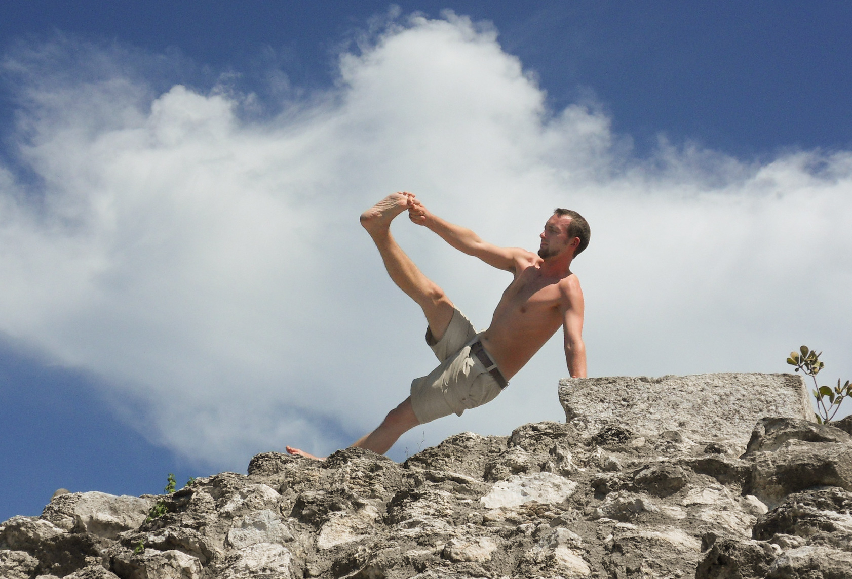 Sebastian Pfaar Seitstütz auf Felsen Yoga Lehrer bei Saya Yoga in Besse