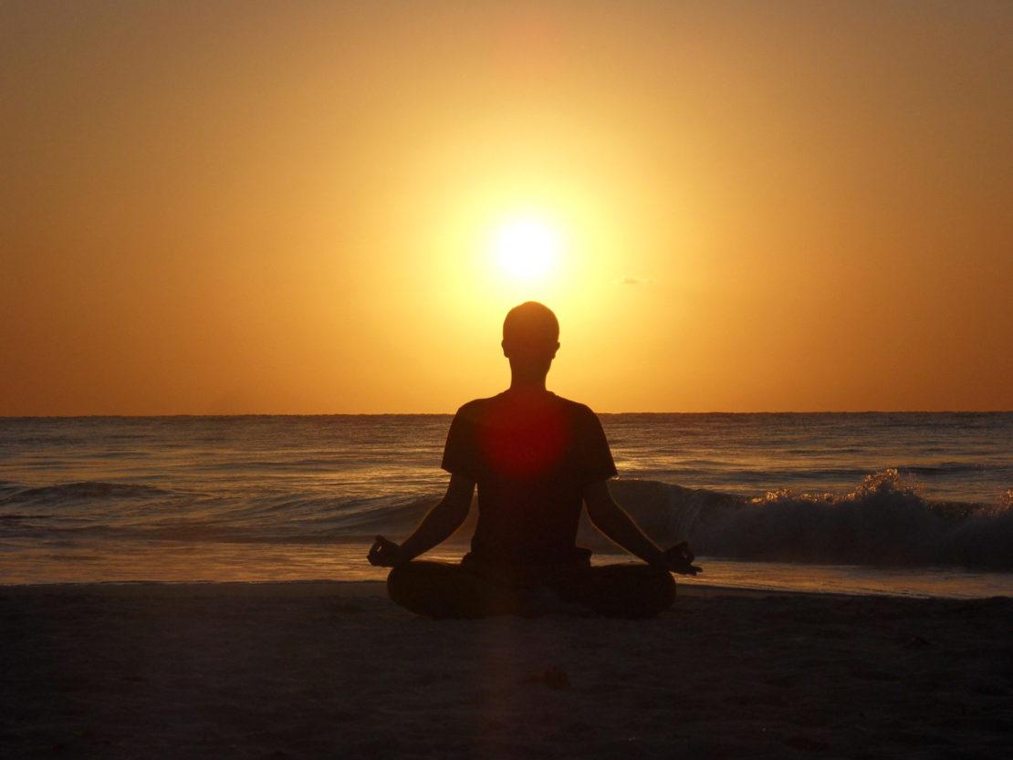 Sebastian Pfaar Meditationshaltung am Strand Yogalehrer bei Satya Yoga in Besse